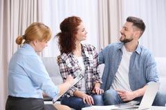 Contrat de signature de jeunes couples se reposant sur le divan Photo libre de droits