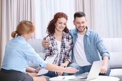 Contrat de signature de jeunes couples se reposant sur le divan Image libre de droits