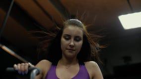 Contratan al atleta atractivo de la muchacha en una bici inmóvil El viento sopla el pelo de una mujer que monta una bici inmóvil almacen de video