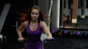 Contratan al atleta atractivo de la muchacha en una bici inmóvil El viento sopla el pelo de una mujer que monta una bici inmóvil metrajes