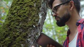 Contratan al botánico en vidrios y con una tableta a la investigación metrajes