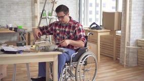Contratan al hombre joven discapacitado en una silla de ruedas con un taladro eléctrico a la reparación almacen de metraje de vídeo