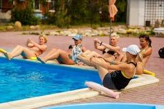 Contratan a la gente a aeróbicos de agua en piscina foto de archivo