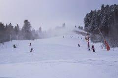 Contratan a la gente al esquí y a la snowboard de la montaña en la pista del esquí imagenes de archivo