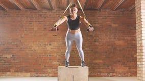 Contratan a la muchacha atlética a tiroteo Un atleta joven se involucra con un trx en el gimnasio almacen de metraje de vídeo