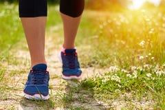 Contratan a la muchacha a funcionamientos cardiios a través del bosque en zapatillas de deporte, sólo las piernas son visibles, l Imagen de archivo