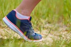Contratan a la muchacha a funcionamientos cardiios a través del bosque en zapatillas de deporte, sólo las piernas son visibles, l Fotografía de archivo libre de regalías