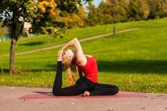 Contratan a la muchacha hermosa joven a yoga, al aire libre en un parque Imagen de archivo