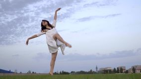 Contratan a la muchacha japonesa hermosa en el vestido blanco a ballet en el césped, a cámara lenta almacen de metraje de vídeo