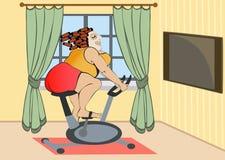 Contratan a la muchacha llena en una bici inmóvil en casa Imagen de archivo libre de regalías
