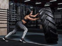 Contratan a la muchacha a un entrenamiento de CrossFit El atleta empuja a Fotos de archivo