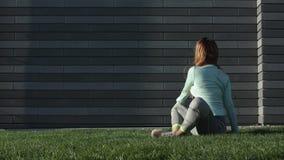 Contratan a la mujer joven a aptitud en la hierba almacen de metraje de vídeo
