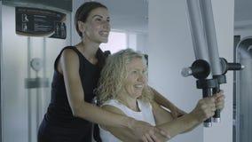 Contratan a la mujer mayor en un simulador al gimnasio con un instructor personal la hija ayuda a la mamá en el gimnasio imagen de archivo libre de regalías