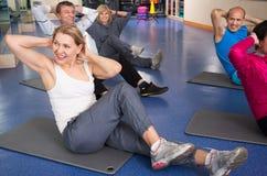Contratan a los hombres y a las mujeres maduros en la estera a gimnasio Fotos de archivo