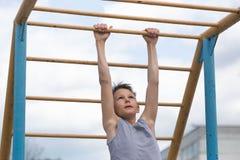 Contratan a un adolescente en una camiseta en gimnasia en una barra horizontal Imagen de archivo libre de regalías