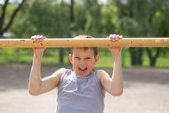 Contratan a un adolescente en una camiseta en gimnasia en una barra horizontal Foto de archivo