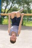 Contratan a un adolescente en una camiseta en gimnasia en una barra horizontal Foto de archivo libre de regalías