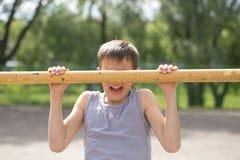 Contratan a un adolescente en una camiseta en gimnasia en una barra horizontal Fotos de archivo