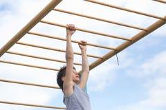 Contratan a un adolescente en una camiseta en gimnasia en una barra horizontal Fotografía de archivo libre de regalías