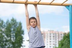 Contratan a un adolescente en una camiseta en gimnasia en una barra horizontal Imagen de archivo