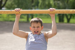 Contratan a un adolescente en una camiseta en gimnasia en una barra horizontal Imagenes de archivo