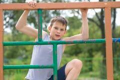 Contratan a un adolescente en una camiseta en gimnasia en una barra horizontal Fotografía de archivo