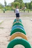 Contratan a un adolescente en una camiseta en la carrera de obstáculos Fotografía de archivo libre de regalías