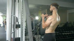 Contratan a un hombre atlético joven con un torso desnudo a trabajo de la comprobación en el gimnasio, sacudiendo los músculos de almacen de video
