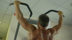 Contratan a un hombre atlético joven con un torso desnudo a trabajo físico en el gimnasio, sacudiendo los músculos de las manos c almacen de video