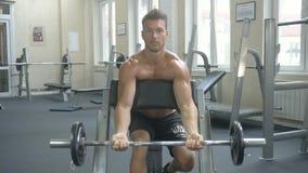 Contratan a un hombre atlético joven con un torso desnudo a trabajo físico en el gimnasio, sacudiendo los músculos de las manos m metrajes
