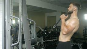 Contratan a un hombre atlético joven con un torso desnudo a trabajo físico en el gimnasio, sacudiendo los músculos de las manos c almacen de metraje de vídeo