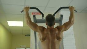 Contratan a un hombre atlético joven con un torso desnudo a trabajo físico en el gimnasio, sacudiendo los músculos de sus manos c almacen de metraje de vídeo
