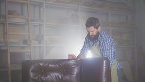 Contratan a un hombre en un delantal con una barba, a muebles de junta en un taller auténtico oscuro almacen de metraje de vídeo