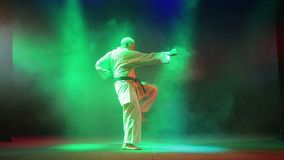Contratan a un hombre en un kimono blanco a karate contra un fondo del humo almacen de video
