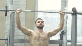 Contratan a un hombre joven con un torso desnudo de una estructura del deporte al gimnasio, haciendo ejercita para los músculos d metrajes