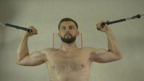 Contratan a un hombre joven con un torso desnudo de una estructura del deporte al gimnasio, haciendo ejercita para los músculos d almacen de video