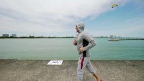Contratan a un hombre joven de los deportes a los deportes, corriendo a lo largo de la costa del lago Cámara lenta almacen de video