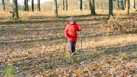 Contratan a una más vieja mujer a parque que camina nórdico almacen de metraje de vídeo