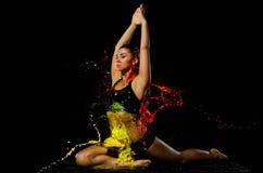 Contratan a una muchacha atlética bañada en pintura amarilla y anaranjada a yoga Imágenes de archivo libres de regalías