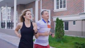Contratan a una mujer atractiva y a su marido adulto a los deportes, cónyuges jovenes funcionados con a lo largo de edificios de  metrajes