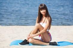 Contratan a una mujer hermosa de los deportes en gimnasia contra la perspectiva del mar Foto de archivo