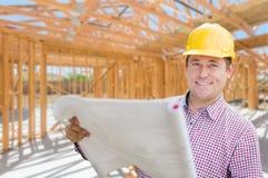 Contratante com planos no local dentro da construção home nova Frami imagens de stock