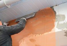 Contratante de construção que emplastra a parede com malha da fibra de vidro, malha do emplastro após a isolação rígida no telhad foto de stock royalty free