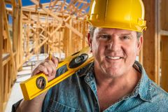 Contratante masculino no capacete de segurança que guardam ao nível e no lápis no Worksite Foto de Stock