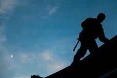 Contratante na silhueta que trabalha em uma parte superior do telhado foto de stock