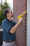 Contratante que enche rachaduras da parede exterior Fotografia de Stock Royalty Free
