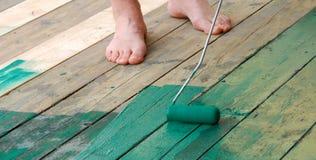 Contrate al pintor que pinta un piso con la pintura verde Foto de archivo libre de regalías