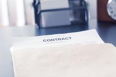 Contrate em um envelope marrom na tabela preta Imagem de Stock