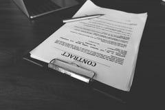 Contrate los papeles y la pluma con el ordenador portátil en el escritorio de madera, contr legal imagen de archivo libre de regalías