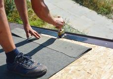 Contratista del Roofer que pega la membrana impermeable en superficie superior del tejado de madera con el cepillo y espray negro fotografía de archivo libre de regalías